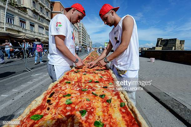 Neapolitan pizza makers attempt to make the longest pizza to break a Guinness World Record along the seafront of Naples on May 18 2016 For the...