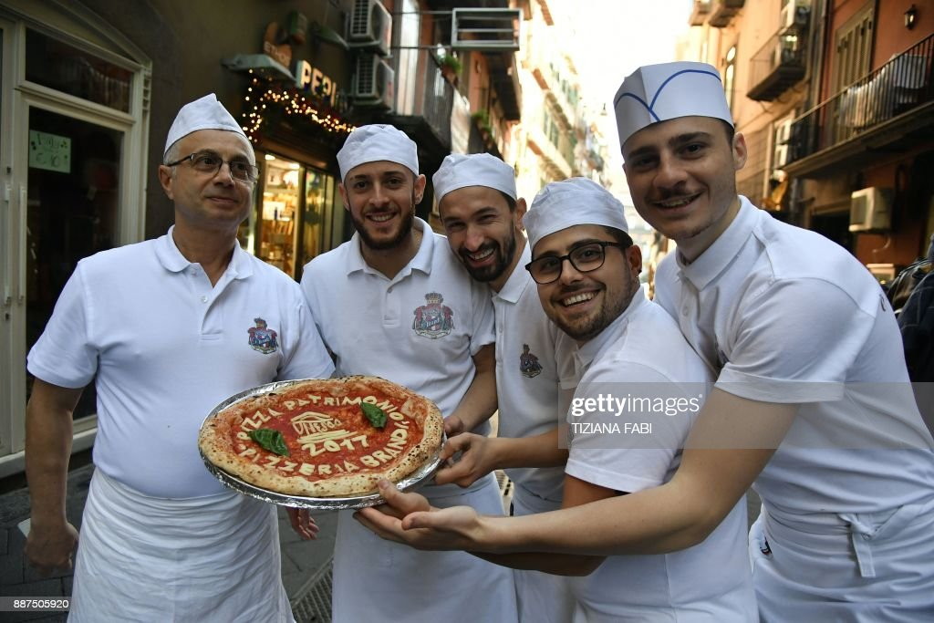 Neapolitan pizza makers pose with a pizza celebrating the Unesco decision to make the art of Neapolitan 'Pizzaiuolo' an 'intangible heritage', on December 7, 2017 outside the Pizzeria Brandi in Naples. The art of the Neapolitan Pizzaiuolo is a culinary practice consisting of four different phases relating to the preparation of the dough and its baking in a wood-fired oven. The practice originates in Naples, where around 3,000 Pizzaiuoli now live and perform, and plays a key role in fostering social gatherings and intergenerational exchange. / AFP PHOTO / Tiziana FABI