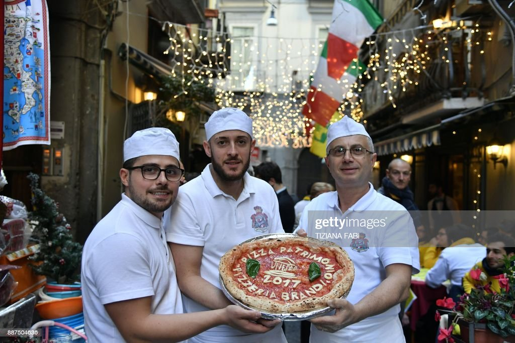 Neapolitan pizza makers pose with a pizza to celebrate the Unesco decision to make the art of Neapolitan 'Pizzaiuolo' an 'intangible heritage', on December 7, 2017 in Naples. The art of the Neapolitan Pizzaiuolo is a culinary practice consisting of four different phases relating to the preparation of the dough and its baking in a wood-fired oven. The practice originates in Naples, where around 3,000 Pizzaiuoli now live and perform, and plays a key role in fostering social gatherings and intergenerational exchange. / AFP PHOTO / Tiziana FABI