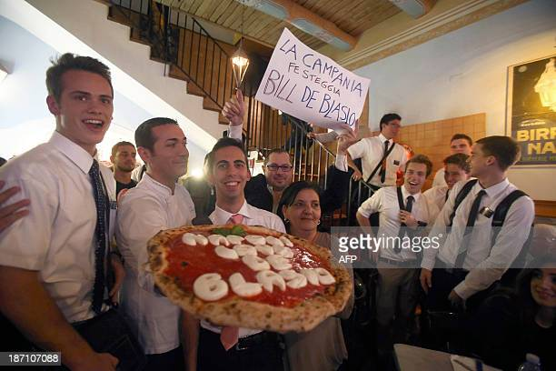 Neapolitan pizzamaker Luigi Sorbillo poses inside his pizzeria with a group of young americans in downtown Naples with the pizza he cooked in honour...