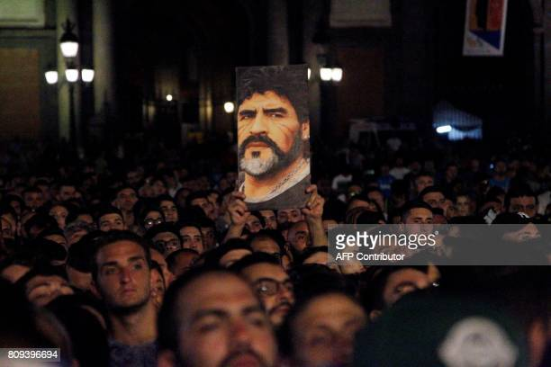 TOPSHOT Neapolitan supporters hold a placard depicting former Argentinian football player Diego Armando Maradona as they greet him during a show at...
