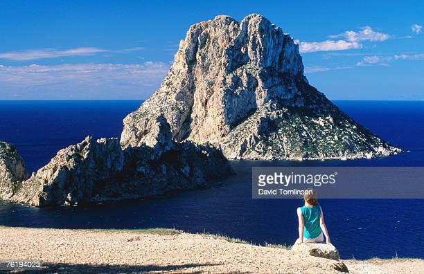 Near Sant Josep de Sa Talaia, girl on rock looking at offshore isle of Es Vedra, Ibiza, Balearic Islands, Spain, Europe