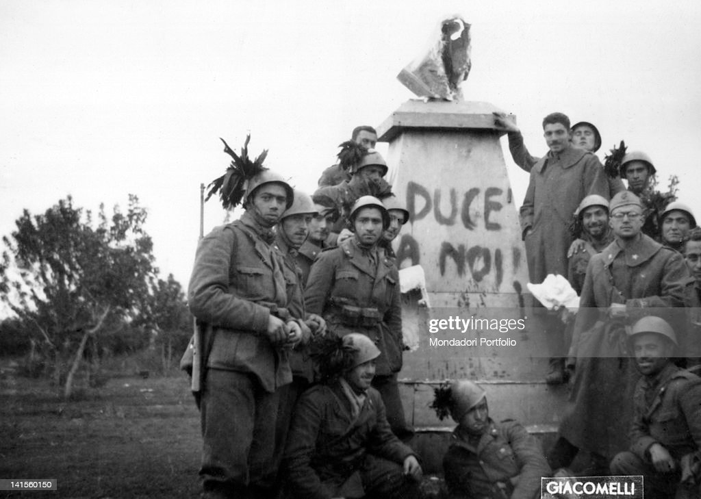 Near the River Donets, on the Russian front, some Italian bersaglieri pose next to ruined statue of Lenin with the words: 'Duce a noi'. October 1941
