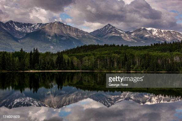 Nearby snowcapped mountains are reflected in Patricia Lake just outside downtown on June 30 2013 near Jasper Alberta Canada Jasper is the largest...