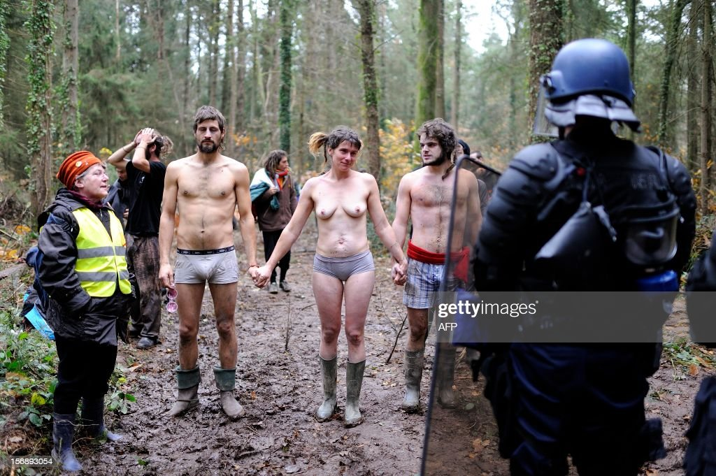 Near-naked protesters face French riot police on November 24, 2012 seeking to evict squatters on protected swampland where Prime Minister Jean-Marc Ayrault wants to build a new airport. Clashes between police and protesters resumed at Notre-Dame-des-Landes, outside the western city of Nantes, as officers fired tear gas and squatters threw stones and glass bottles at them in return.