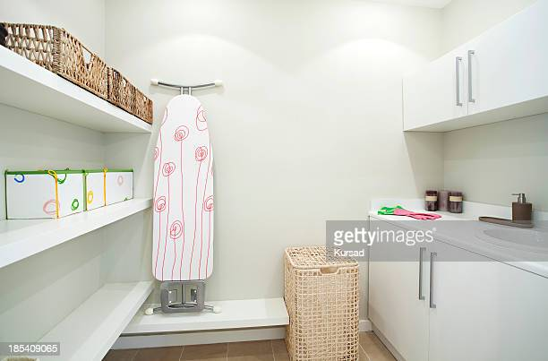 Neat and clean laundry room with hamper and ironing board