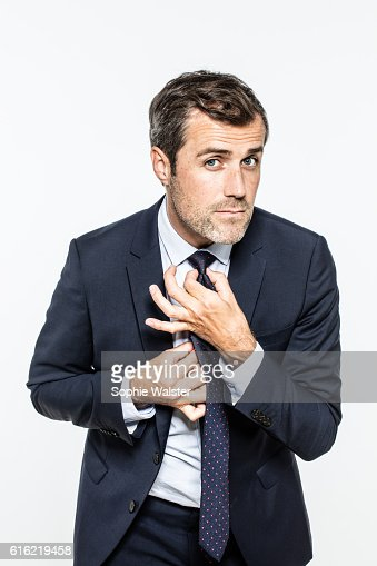 neat bearded businessman adjusting his fashionable knot for smart career : Foto stock