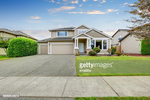 Neat beige home with two garage spaces. : Stock Photo