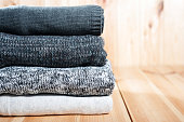 A neat pile of knitted warm blanket or sweaters gray, white on a wooden background. Comfort, warmth and a homely atmosphere in the cold winter. Copyspace