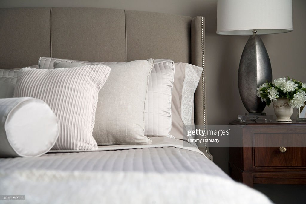 Neatly arranged pillows on a bed : Stock Photo