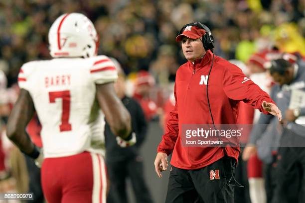 Nebraska Cornhuskers defensive line coach John Parrella high fives players as they exit the field during the Big Ten conference game between the...