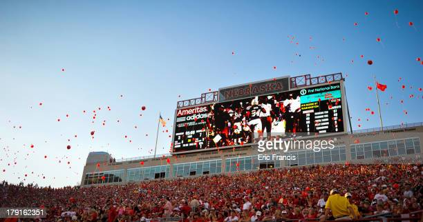 Nebraska fans release red balloons after the Nebraska Cornhuskers score their first points of the game against the Wyoming Cowboys at Memorial...