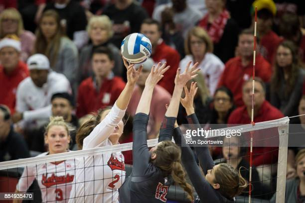 Nebraska outside hitter Mikaela Foecke hits the ball over Washington State middle blocker Claire Martin and Washington State setter Ashley Brown in...