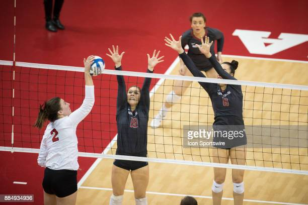 Nebraska outside hitter Mikaela Foecke spikes the ball against Washington State setter Ashley Brown and Washington State middle blocker Jocelyn Urias...