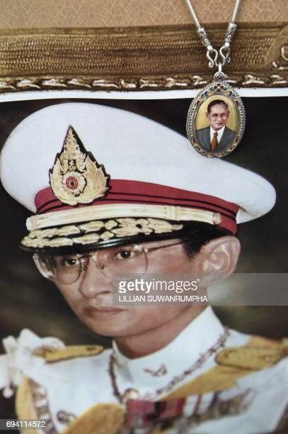 A necklace depicting Thai King Bhumibol Adulyadej is seen as a woman holds a photograph of the late monarch at the King Rama V Monument in Bangkok on...