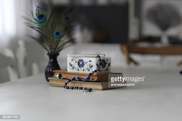 Necklace, jewelry box and books on table