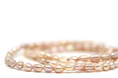 Necklace of pink river pearls isolated on white background. Photo of Macro shot of jewelry. Luxury wedding background.