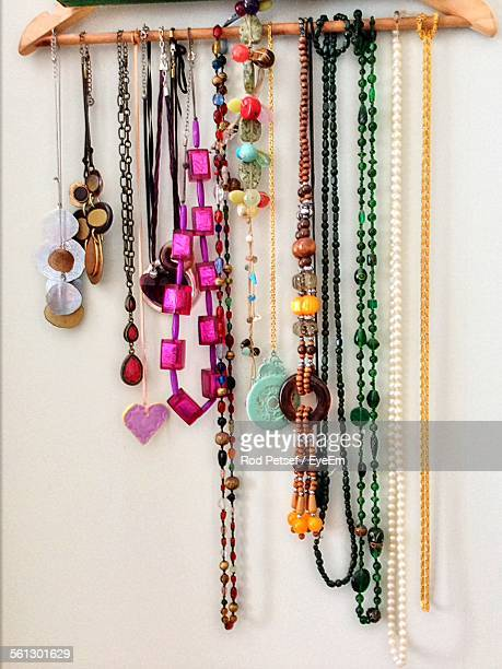 Necklaces Hanging From Coathanger On Wall