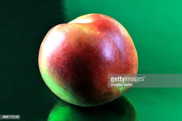 Nectarine fruit on a green background (Prunus persica)
