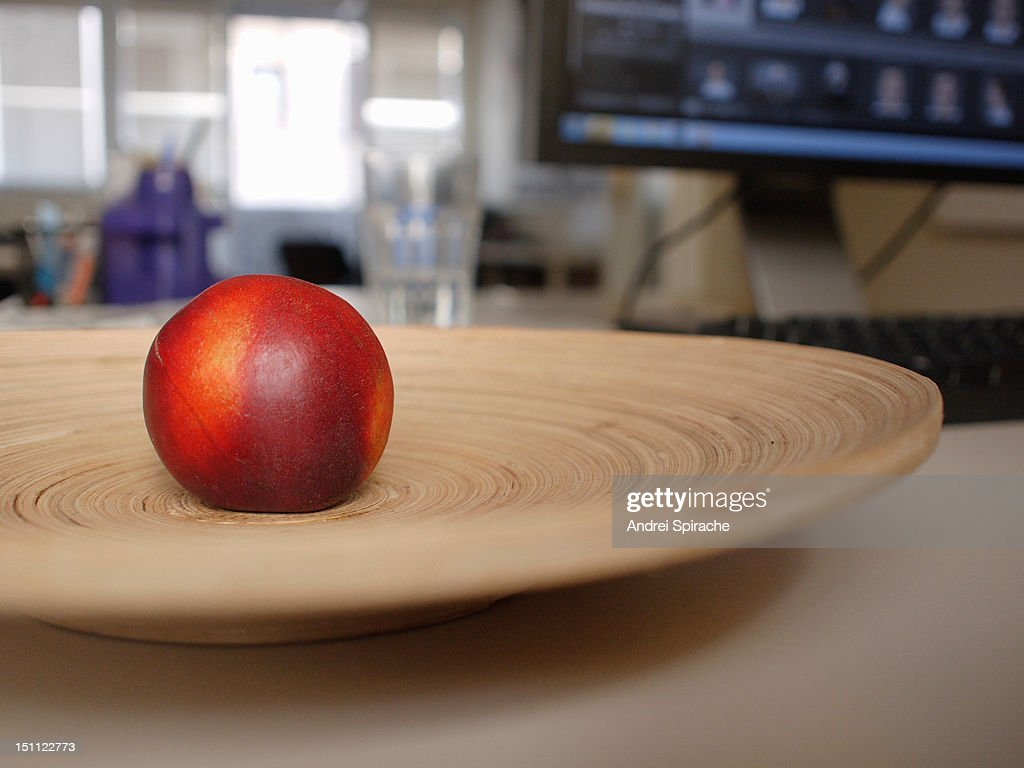 Nectarine on a wooden plate in an office : Stock Photo