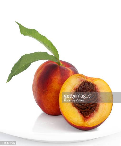 Nectarine with leaves and one cut to reveal stone