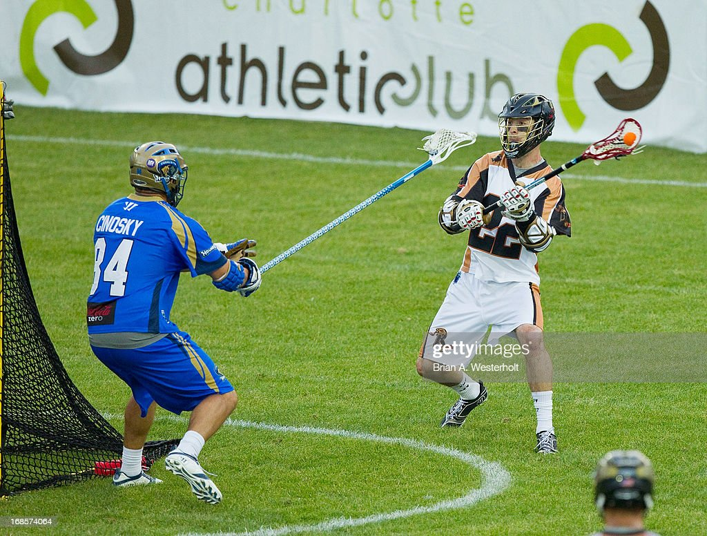 Ned Crotty #22 of the Rochester Rattlers looks to make a pass from behind the goal while being defended by Joe Cinosky #84 of the Charlotte Hounds at American Legion Memorial Stadium on May 11, 2013 in Charlotte, North Carolina. The Rattlers defeated the Hounds 13-10.