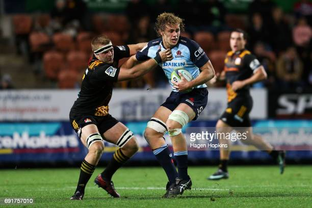 Ned Hanigan of the Waratahs is tackled by Sam Cane of the Chiefs during the round 15 Super Rugby match between the Chiefs and the Waratahs at Waikato...
