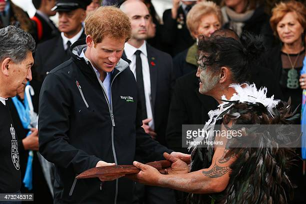 Ned Tapa presents Prince Harry with a carved wooden Maori paddle prior to paddling a waka on the Whanganui River after a visit to Putiki Marae on May...