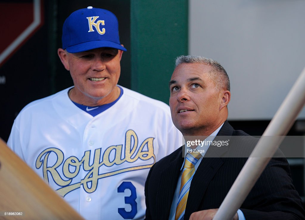 Ned Yost #3 manager of the Kansas City Royals talks with general manager Dayton Moore prior to a game against the New York Mets on opening day at Kauffman Stadium on April 3, 2016 in Kansas City, Missouri.