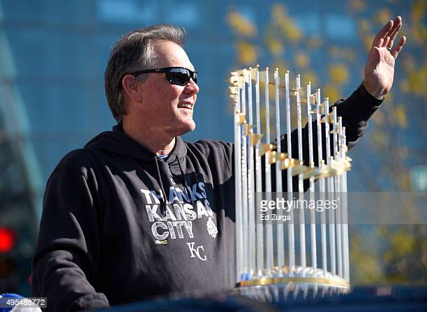 Ned Yost manager of the Kansas City Royals waves to fans as he rides with the championship trophy during a parade to celebrate their World Series...