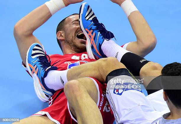 TOPSHOT Nedim Remili of France fights for the ball with Marko Mamic of Croatia during their Main Round match of the Men's 2016 EHF European Handball...