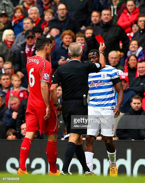 Nedum Onuoha of QPR is shown the red card by referee Martin Atkinson during the Barclays Premier League match between Liverpool and Queens Park...