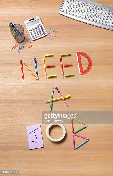 'Need a job' written with objects on a desk