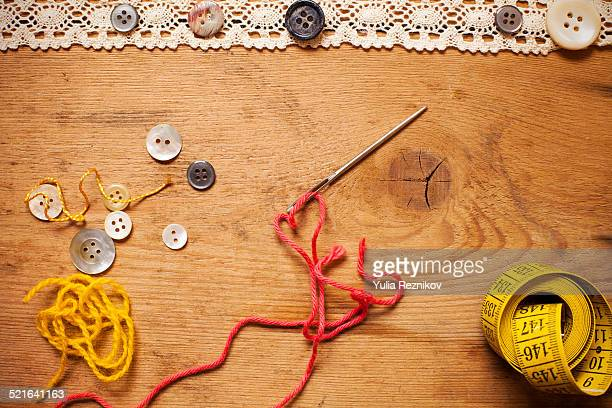 Needle, buttons,thread on the wood background