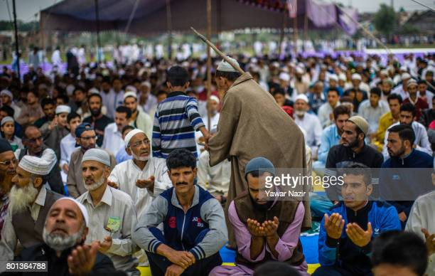 A needy asks for alms as Kashmiri Muslims wait to offer congregational EidulFitr prayers at Eid Gah on Eidulfitr a festival of Muslims on June 26...