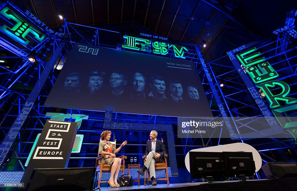 Neelie Kroes and Apple CEO Tim Cook take part in a panel discussion during the kickoff of Startup Fest Europe on May 24 2016 in Amsterdam The...