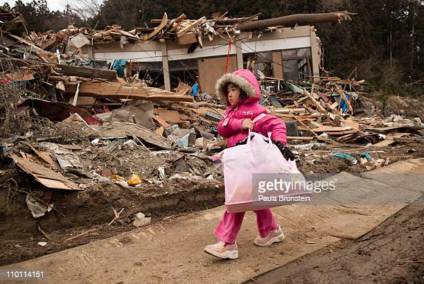 Neena Sasaki carries some of the family belongings from her home that was destroyed after the devastating earthquake and tsunami on March 15 2011 in...