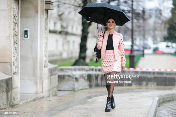Negin Mirsalehi fashion blogger wears a black top a pink jacket a pink skirt black tights and black leather boots outside the Elie Saab show during...