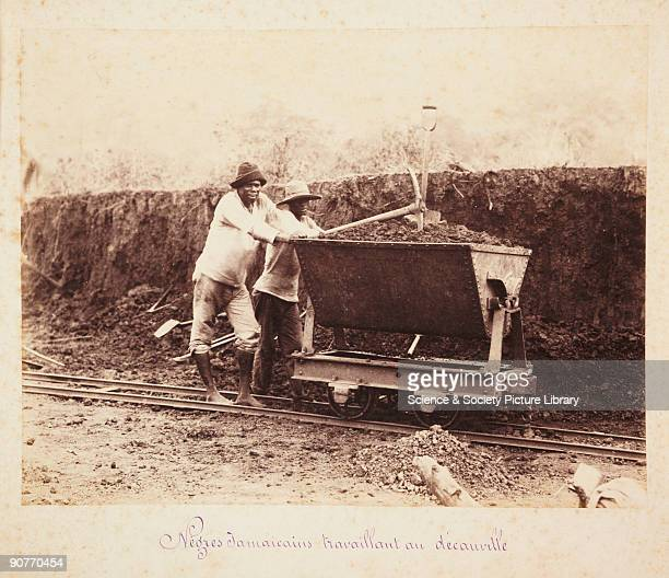 'Negre Jamaicains travaillant au decauville' A photograph of two Jamaican workers pushing a wagon full of earth on a decauville railway a narrowgauge...
