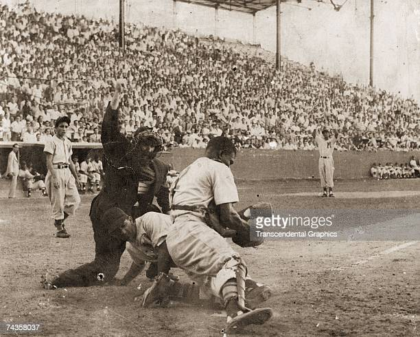 HAVANA C1950 Negro League catcher Ray Noble of the Cienfuegos team puts a tag on a sliding Havana Lions player in a game at Tropical Stadium in...