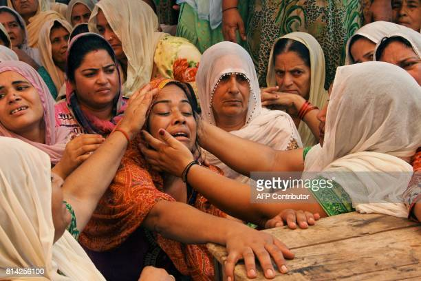 Neha Devi wife of slain Indian soldier Lance Naik Ranjeet Singh is consoled by relatives at his home in Burn village about 28km from Jammu on July 14...