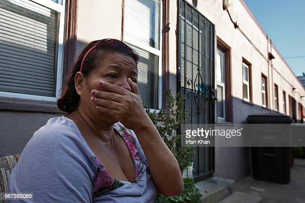 JANUARY 13 2015 A neighbor Idelfonsa Cruz covers her face to avoid leftover stench coming next door apartment where three people were found dead...