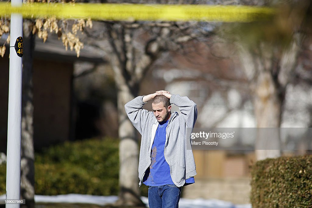 A neighbor takes in the scene at a town home where four people were killed Saturday morning including the gunman who held police at bay for several hours at the complex January 5, 2013 in Aurora, Colorado. Aurora SWAT team members shot a gunman after he went to a second-floor window and fired at police. The gunman also allegedly fatally shot two men and a woman that he had taken hostage. One woman managed to escape from an upstairs back window, ran from the home and called police just before 3 a.m., said Cassidee Carlson, Aurora police spokeswoman.