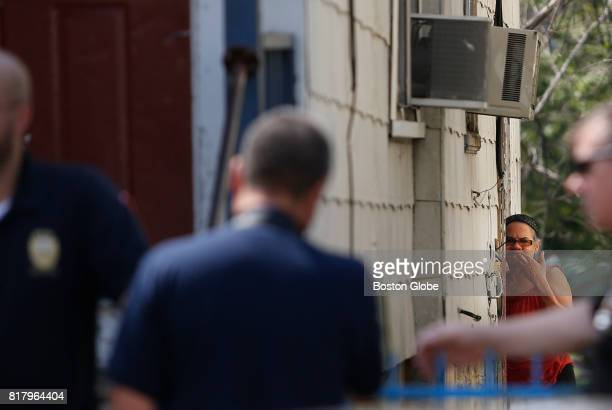 A neighbor watches as police and fire respond to the scene of an overdose that killed two people in Lawrence MA on Jul 17 2017 The victims were...