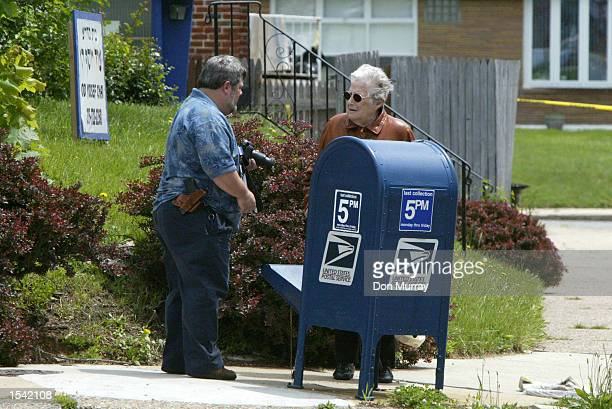 A neighborhood resident speaks to an investigator after Philadelphia Police FBI and Postal Police investigated the contents of a US Mail box May 14...