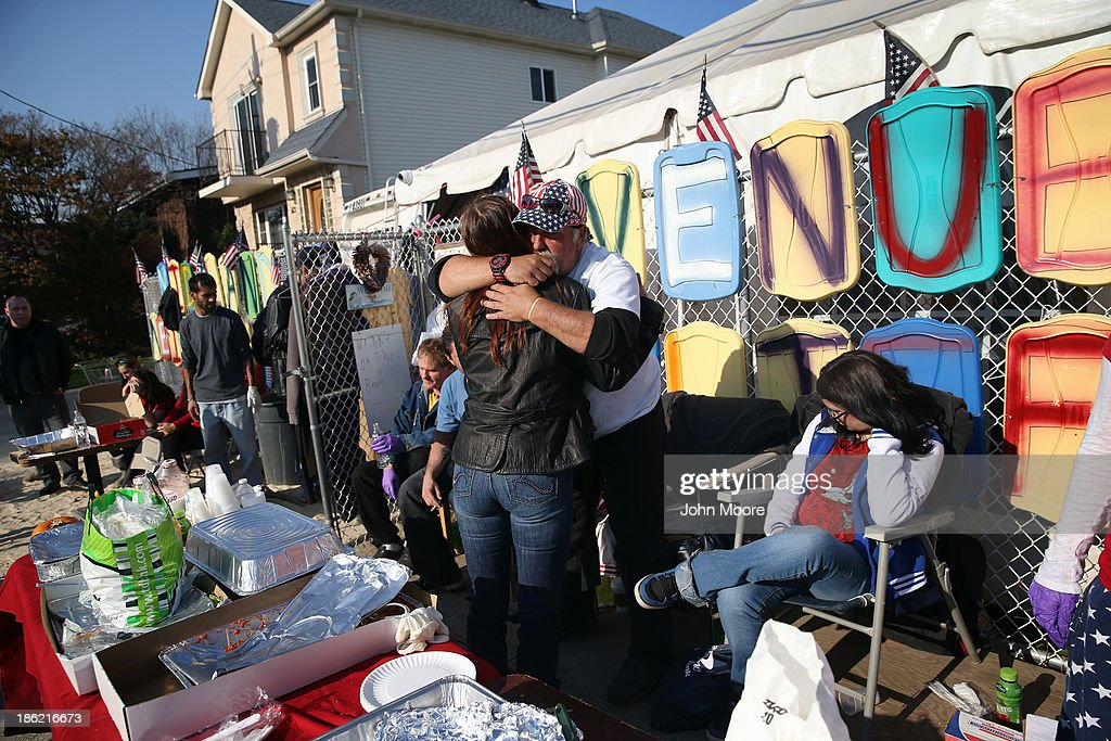 Neighborhood residents embrace outside the Midland Avenue Neighborhood Relief center on October 29, 2013 in the Midland Beach area of the Staten Island borough of New York City. The center has been operating the full year since Superstorm Sandy, aiding local residents with free clothing, food and baby/infant products.