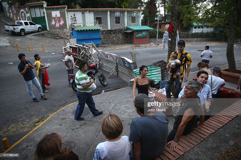 Neighborhood residents gather around a barricade on March 7, 2014 in San Cristobal, Venezuela. Anti-goverment protesters have set up barricades throughout San Cristobal, the capital of Venezuela's Tachira state, bordering Colombia. The state has been a focal point for anti-government protests for almost a month.