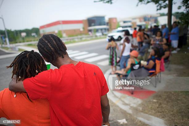 Neighborhood residents gather with friends across the street from where President Barack Obama will deliver a speech at the Salvation Army Ray Joan...