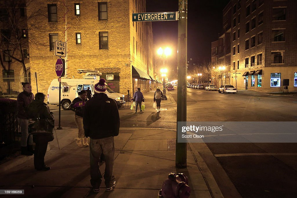Neighborhood residents watch as Chicago police investigate the scene where two men were shot in the Old Town neighborhood on January 8, 2013 in Chicago, Illinois. Tyshawn Blanton, 31, died as a result of the shooting and a 20-year-old man who was shot in the back was taken to the hospital in serious-to-critical condition. Blanton's murder was at least the 14th murder in the city this year. The Old Town neighborhood was selected last month by Realtor.com as 2012's hottest neighborhood in the country. Today Vice President Joe Biden will be meeting with victims' groups and gun-safety organizations at the White House in his effort to develop proposals to curb gun violence following the Sandy Hook school shooting in Newtown, Connecticut. Tomorrow he is expected to meet with the NRA.