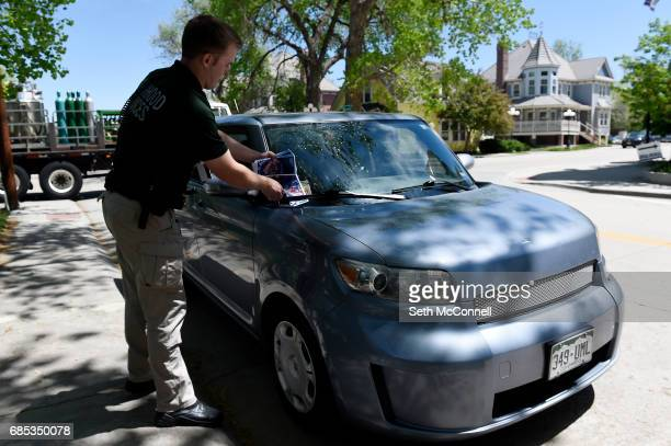 Neighborhood Service Officer Ryley Davis places information pamphlets on the new parking restrictions on the windshields of cars along South Pikes...